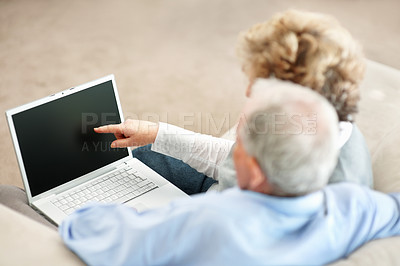 Buy stock photo Rearview of a senior couple sitting on a sofa at home while the wife points at a blank laptop screen