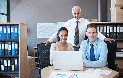 Buy stock photo Mature businessman standing proudly behind two seated staff members, confidently smiling at the camera