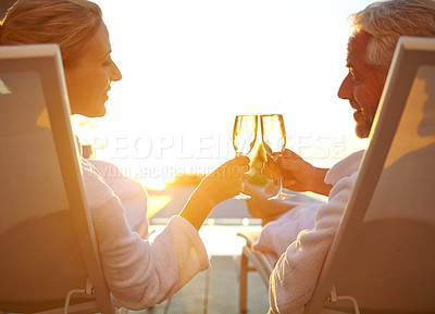 Buy stock photo Rearview shot of a mature couple drinking champagne while relaxing in deck chairs at sunset