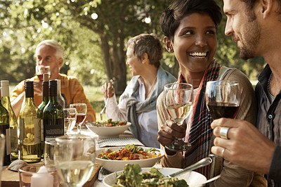 Buy stock photo Shot of a happy young couple enjoying an outdoor meal with family