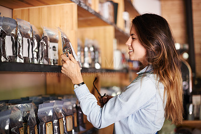 Buy stock photo Shot of a beautiful smiling woman in a store choosing a packet of coffee beans