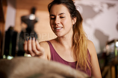 Buy stock photo Shot of a beautiful smiling woman looking at a handful of fresh coffee beans