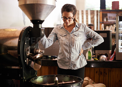 Buy stock photo Shot of a young woman using an old-fashioned coffee roasting machine