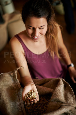 Buy stock photo Overhead shot of a young woman holding a handful of fresh coffee beans