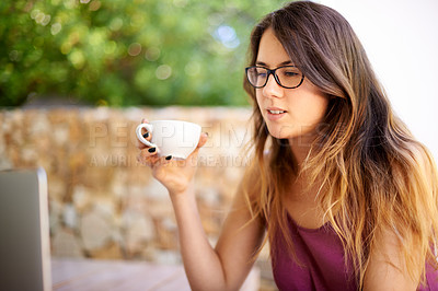 Buy stock photo Shot of a beautiful young woman looking at her laptop, while having coffee outside