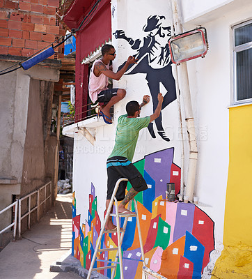 Buy stock photo Shot of two young graffiti artists painting a design on a wall