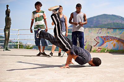 Buy stock photo Shot of a group of young people watching a breakdancer in the streets