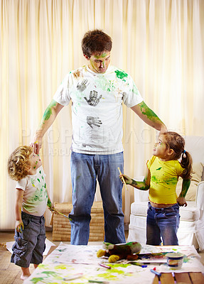 Buy stock photo Shot of a paint covered father scolding his children for making a mess