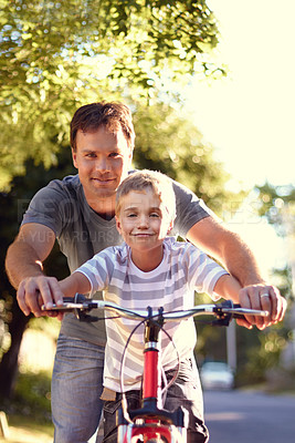 Buy stock photo Shot of a father and son spending quality time together with a bicycle