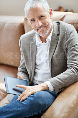 Buy stock photo Portrait of a handsome mature man sitting on the sofa with his digital tablet
