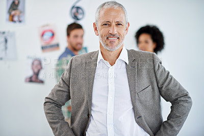 Buy stock photo Portrait of a handsome businessman standing with his employees behind him. The commercial designs displayed in this image represent a simulation of a real product and have been changed or altered enough by our team of retouching and design specialists so that they are free of any copyright infringements