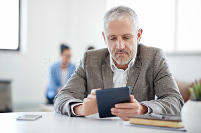 Buy stock photo Shot of a mature businessman using a digital tablet while sitting at a table in an office