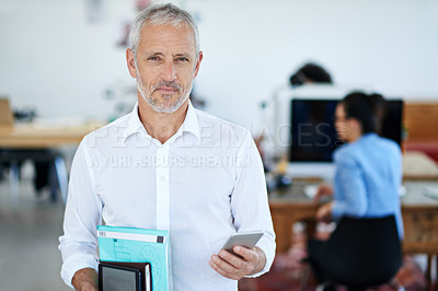Buy stock photo Portrait of a mature businessman using a cellphone while standing in an office