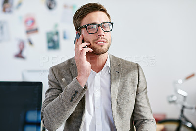 Buy stock photo Shot of a handsome businessman talking on his cellphone in the office. The commercial designs displayed in this image represent a simulation of a real product and have been changed or altered enough by our team of retouching and design specialists so that they are free of any copyright infringements