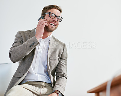 Buy stock photo Shot of a handsome businessman talking on his cellphone in the office