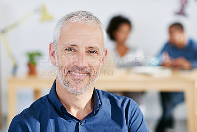Buy stock photo Portrait of a handsome businessman sitting in his office. The commercial designs displayed in this image represent a simulation of a real product and have been changed or altered enough by our team of retouching and design specialists so that they are free of any copyright infringements