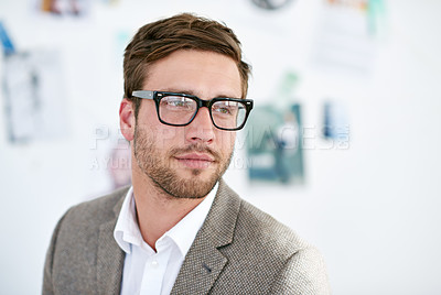 Buy stock photo Shot of a young man standing in an office. The commercial designs displayed in this image represent a simulation of a real product and have been changed or altered enough by our team of retouching and design specialists so that they are free of any copyright infringements