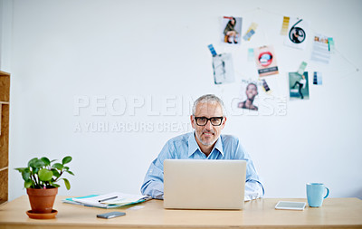Buy stock photo Portrait of a handsome businessman working on his laptop. The commercial designs displayed in this image represent a simulation of a real product and have been changed or altered enough by our team of retouching and design specialists so that they are free of any copyright infringements