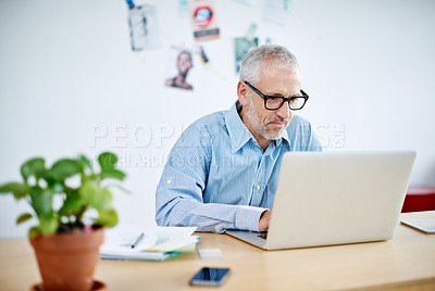 Buy stock photo Shot of a handsome businessman working on his laptop. The commercial designs displayed in this image represent a simulation of a real product and have been changed or altered enough by our team of retouching and design specialists so that they are free of any copyright infringements