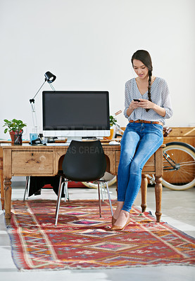 Buy stock photo Shot of an attractive female designer sending a text from her modern office