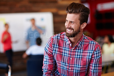 Buy stock photo Shot of a cheerful young male designer in a casual work environment