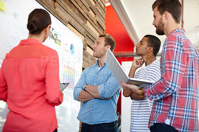 Buy stock photo Shot of a group of young designers brainstorming at a whiteboard