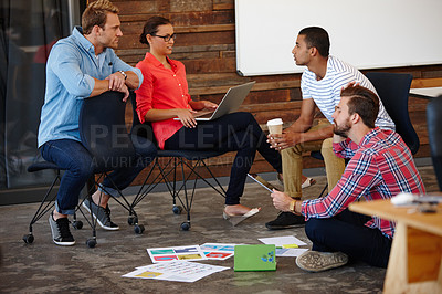 Buy stock photo Shot of a group of young designers having an informal meeting
