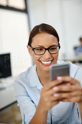 Buy stock photo Shot of a young woman smiling while using her cellphone at work