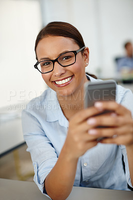 Buy stock photo Portrait of a young woman sitting with her cellphone at work