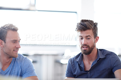 Buy stock photo Shot of two male colleagues discussing work in the office