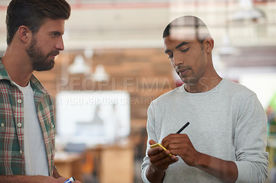 Buy stock photo Shot of two colleagues discussing ideas together
