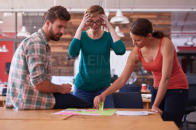 Buy stock photo Shot of a group of young creatives talking around a table