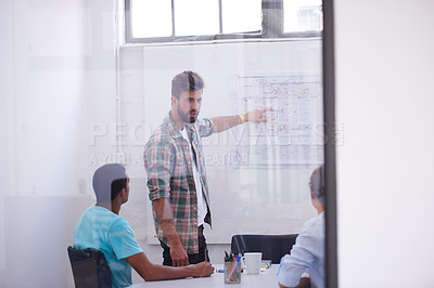 Buy stock photo Shot of a handsome young man working in his office