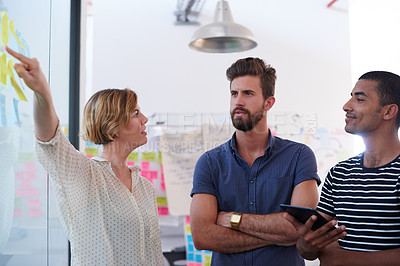 Buy stock photo Shot of a group of colleagues discussing ideas together on sticky notes