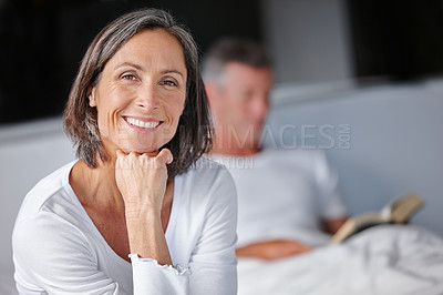 Buy stock photo Portrait of an attractive mature woman sitting on her bed with her husband in the background