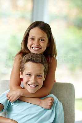 Buy stock photo Shot of a little girl embracing her brother from behind
