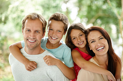Buy stock photo Portrait of a happy family of four spending time together outdoors