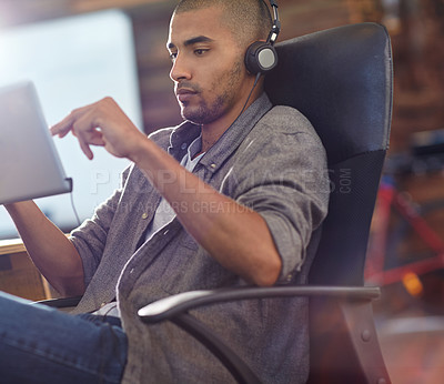 Buy stock photo Shot of a designer listening to music on a digital tablet in an office
