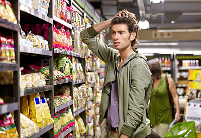 Buy stock photo A young man with his hands in his hair looking confused