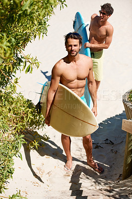 Buy stock photo Two young male friends leaving the beach after a surf