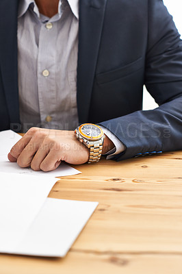 Buy stock photo Cropped shot of a businessman resting his arm on his desk checking the time on his watch