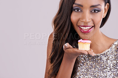 Buy stock photo Studio shot of a gorgeous  young woman holding a cupcake against a gray background