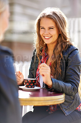 Buy stock photo Two young girlfriends meeting at a cafe for coffee and a chat
