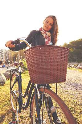 Buy stock photo A beautiful woman standing with her bicycle outside