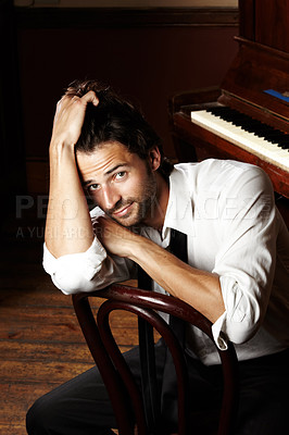 Buy stock photo Portrait of a young musician sitting in front of his piano