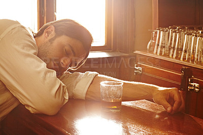 Buy stock photo A handsome young man sleeping on the counter at a bar