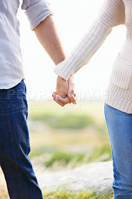 Buy stock photo Cropped image of a loving couple holding hands