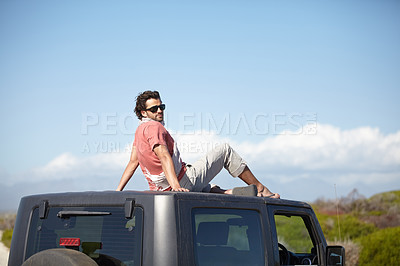 Buy stock photo A young man sits on the car roof