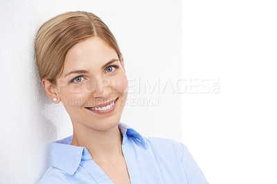 Buy stock photo Studio shot of a beautiful young businesswoman leaning against a white wall