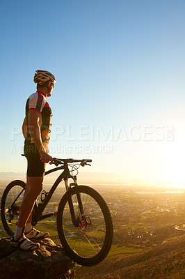 Buy stock photo Full length shot of a man looking at the view whule cycling in the mountains